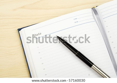 Opened notebook and a pen on it - stock photo