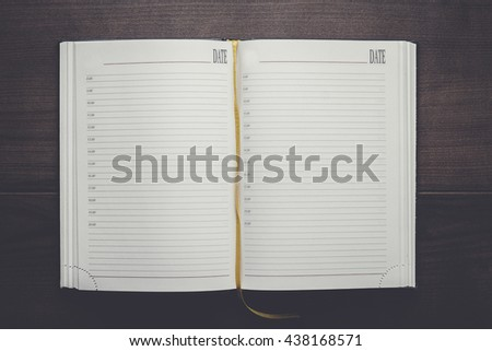 opened notebook on the brown wooden table - stock photo