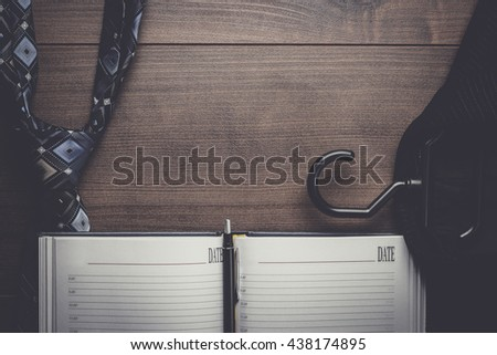 opened notebook on the table with suit and tie - stock photo
