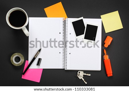 Opened notebook, photos and other on black office desk. - stock photo