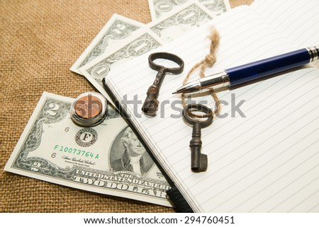 Opened notebook with a blank sheet, pen, keys and money on the old tissue - stock photo