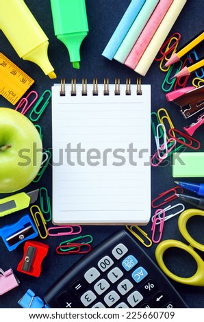 Opened notebook with pencil and colorful school tool supplies surrounding on the blackboard. Back to school concept - stock photo