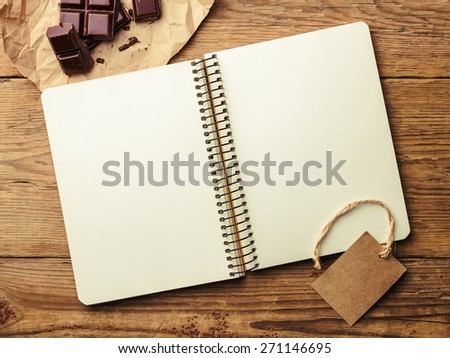 Opened notepad and chocolate on vintage wooden table. Top view - stock photo
