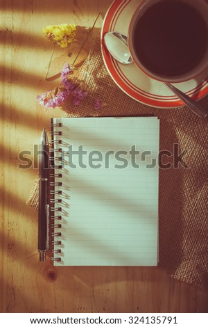 Opened notepad with blank area for text or message, pen, and a cup of hot tea on wood table in cafe with light effect from window in morning time with film filter effect