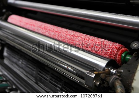Opened offset printing machine with ink rollers with special red wetting roller. Focused to right side image. - stock photo