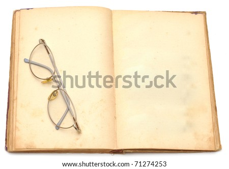 opened old book with eyeglass isolated on white background - stock photo