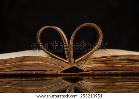 Opened old book with reflected in black surface - stock photo