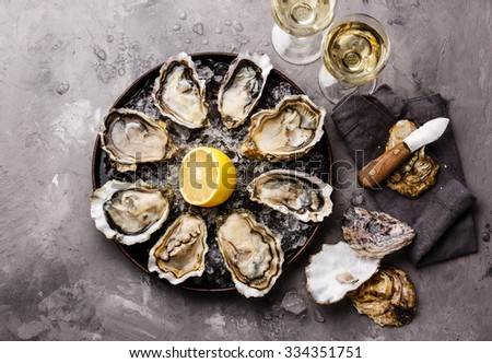Opened Oysters Fines de Claire on plate and white wine on gray concrete texture background - stock photo