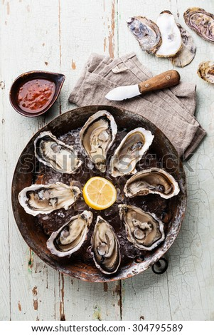 Opened Oysters on metal copper plate on blue wooden background with spicy sauce and oyster knife - stock photo