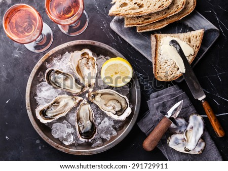 Opened Oysters on metal plate with dark bread with butter and rose wine on dark marble background  - stock photo