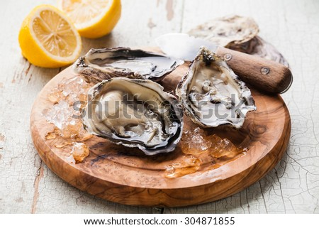 Opened Oysters on olive wood board on blue wooden background with lemon and oyster knife - stock photo