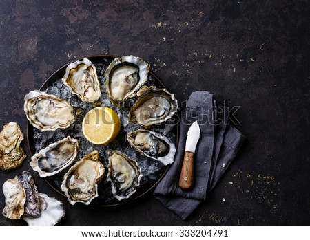 Opened Oysters Speciale de Claire on plate on dark black stone texture background - stock photo