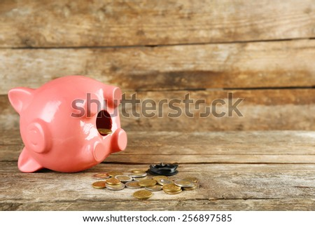 Opened piggy bank with coins on old wooden table - stock photo