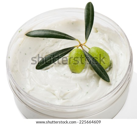 Opened plastic container with cream and green olives with leaves isolated on a white background. - stock photo