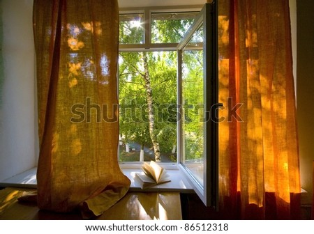 Opened plastic window  with book open and view to green trees - stock photo