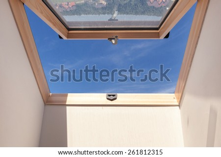 Opened roof window dormer with white wall against blue sky - stock photo