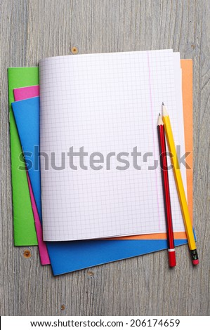 Opened school notebooks and pencils on the desk - stock photo