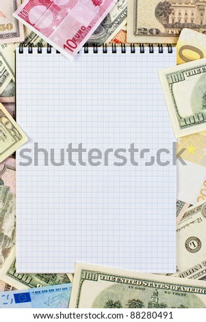 Opened spiral notepad (notebook) sheet in a cage on money background ( euro and dollars cash)