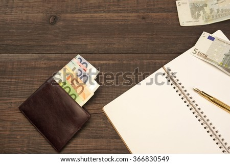 Opened Spiral Notepad With Blank White Page, Golden Fountain Pen And Wallet With Euro Cash On The Rough Wood Table Background With Copy Space, Top View - stock photo