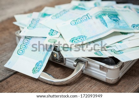 Opened steel case with Russian banknotes inside on wooden floor - stock photo