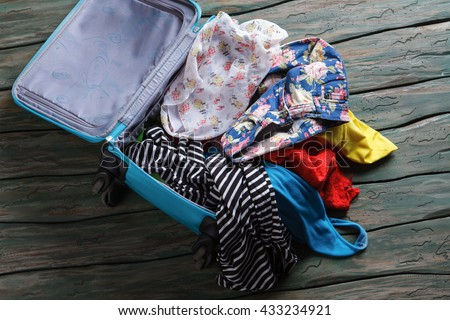 Opened suitcase with clothes. Crumpled clothes inside luggage bag. You have forgotten something. Leaving home in a hurry. - stock photo