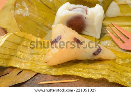 opened Thai dessert sticky rice wrapped in banana leaf on wood background.Thailand style food