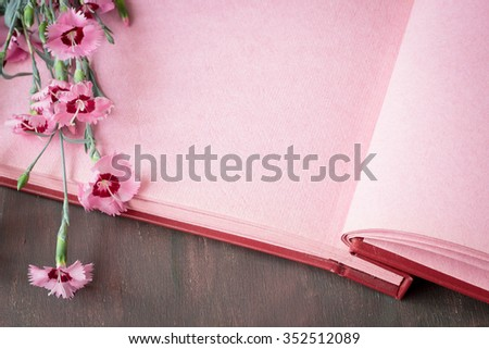 Opened vintage photo album with pink pages on wooden table, sweet william flowers, space for romantic text, selective focus - stock photo