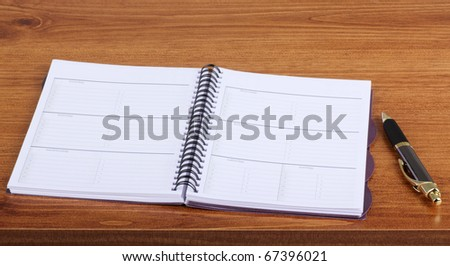 Opened weekly planner on a desk with a pen - stock photo