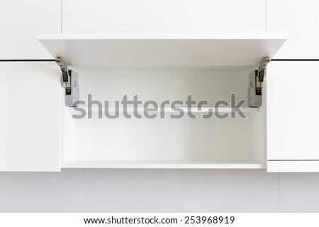 opened white kitchen cabinet with empty shelf - stock photo