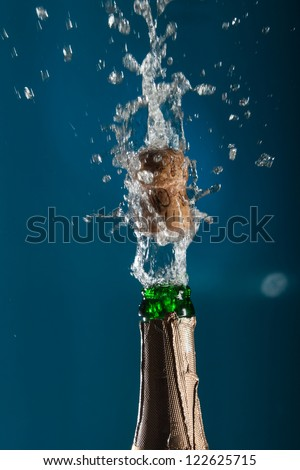 Opening a bottle of champagne with splashes - stock photo