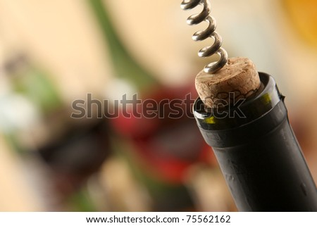 Opening a wine bottle with a corkscrew - stock photo