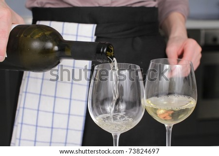 Opening a wine bottle with corkscrew in a kitchen - stock photo