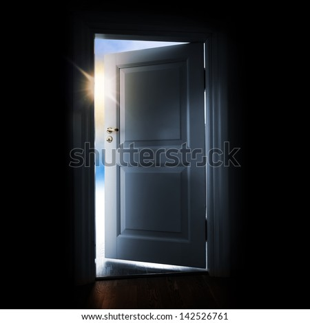 Opening blue door in a dark room with shining light and sky outside - stock photo