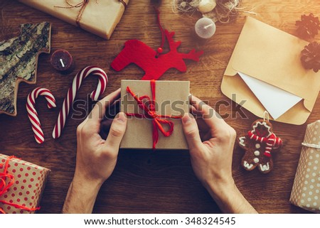 Opening Christmas present. Close-up top view of man opening gift box on the wooden desk with Christmas decorations laying around - stock photo
