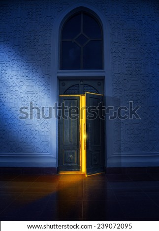 Opening door with yellow glow in the church at night  - stock photo