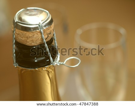 Opening the bottle of champagne. Focus on the cork, shallow DOF. - stock photo