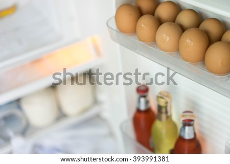 opening the fridge at home in the kitchen selective focus on eggs  - stock photo