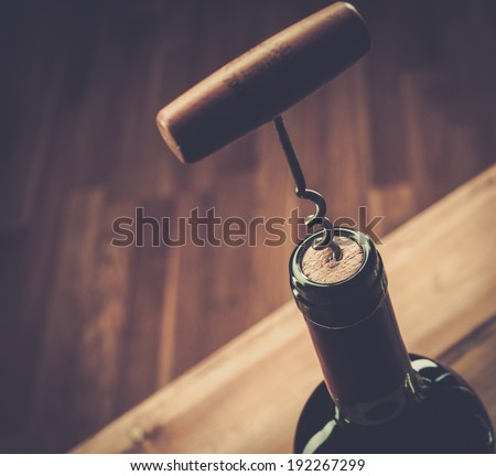 Opening wine bottle with a corkscrew  - stock photo