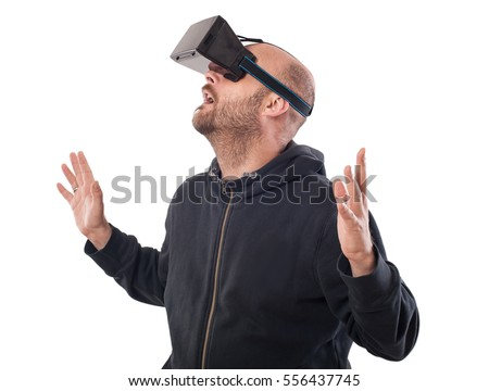 Openmouthed and excited man play game with virtual reality device. Studio shoot. Isolated