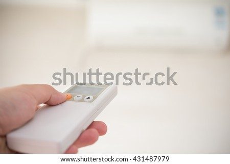 operating a remote control directed on the conditioner - stock photo