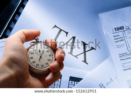Operating budget, calendar, tax and stopwatch in hand - stock photo