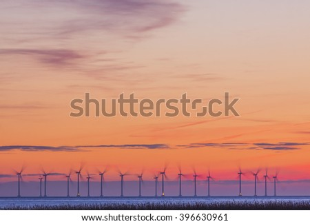 Operating offshore wind power station in sunset over Oresund between Denmark and Sweden - stock photo