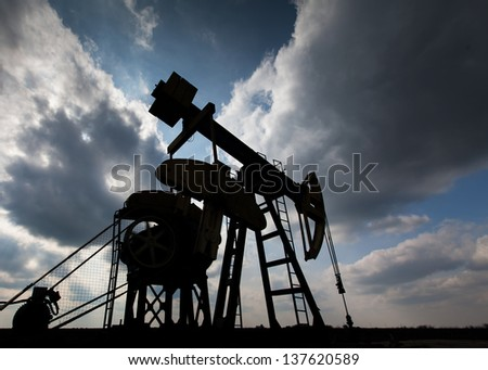 Operating oil and gas well contour, profiled on sky with storm clouds - stock photo