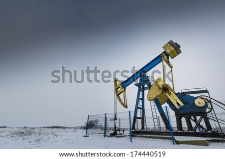 Operating oil and gas well detail profiled on white and grey sky - stock photo