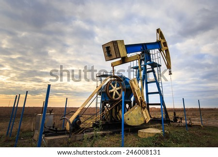 Operating oil and gas well profiled on dramatic sky - stock photo