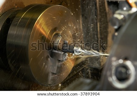 Operation of drilling a hole in on turning machine with metal-working coolant - stock photo