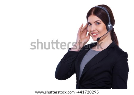 Operator at work. Confident young customer service worker adjusting her headset and smiling while standing against white background - stock photo