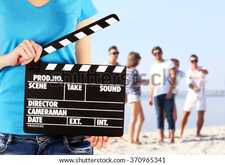 Operator holding clapperboard during the production of film outdoor - stock photo