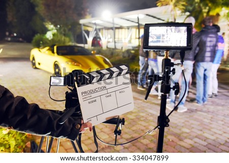 Operator holding clapperboard during the production of short film outdoor in the night with sportive yellow car and actor on stage. Focus on the clapperboard and monitors - stock photo