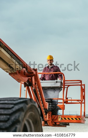 Operator In Safety Helmet and red square shirt controlling Straight Boom Lift - stock photo